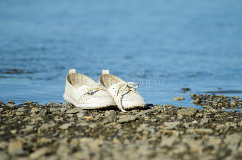 White shoes left the seashore stock image