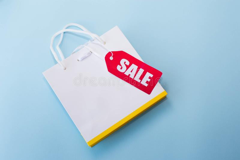 White shopping bag with red label sale on blue background. copy space.  stock images