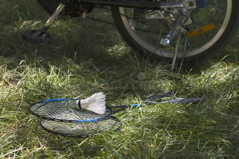 White shuttlecock with rackets on green grass and wheel of electric bicycle on the background. Sunny day. Selective focus royalty free stock images