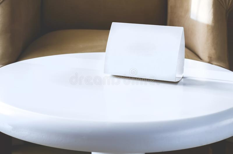 White sign cardboard with copy space on a white round table. Hotel interior royalty free stock photography