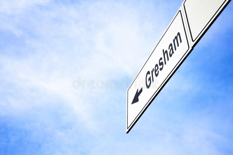 Signboard pointing towards Gresham. White signboard with an arrow pointing left towards Gresham, Oregon, USA, against a hazy blue sky in a concept of travel stock photo