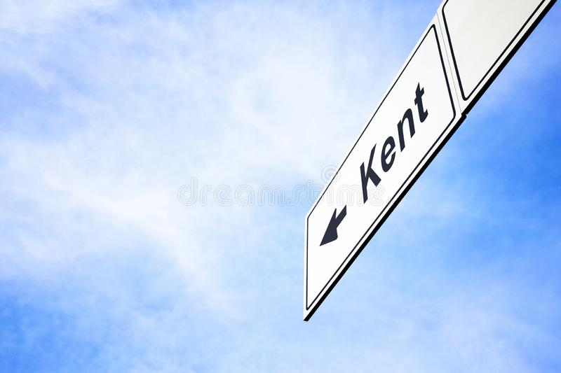 Signboard pointing towards Kent. White signboard with an arrow pointing left towards Kent, Washington, USA, against a hazy blue sky in a concept of travel stock image