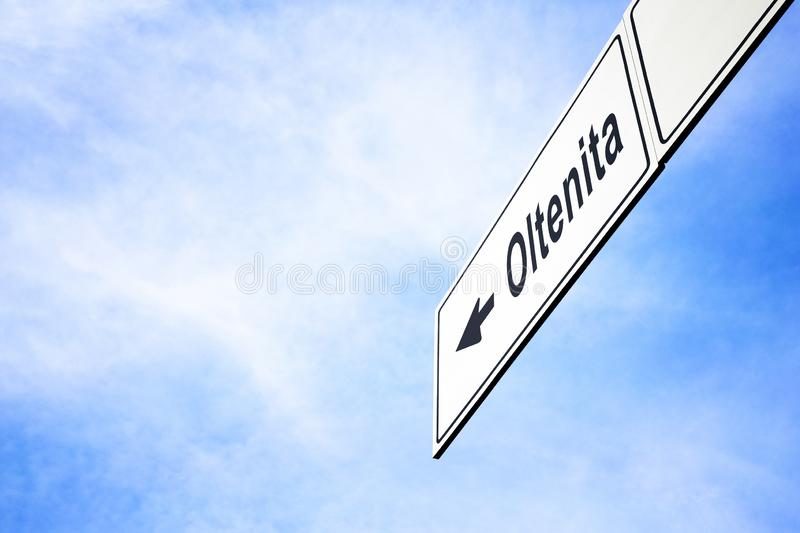 Signboard pointing towards Oltenita. White signboard with an arrow pointing left towards Oltenita, Romania, against a hazy blue sky in a concept of travel stock photos