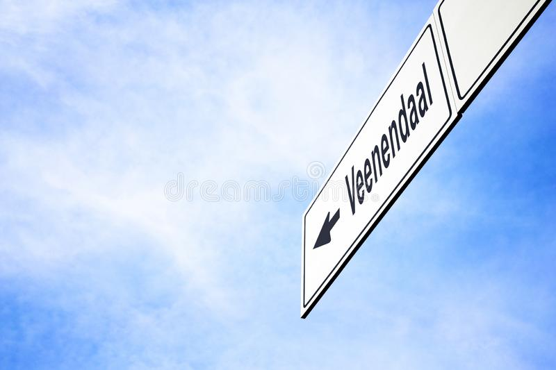 Signboard pointing towards Veenendaal. White signboard with an arrow pointing left towards Veenendaal, Netherlands, against a hazy blue sky in a concept of stock images