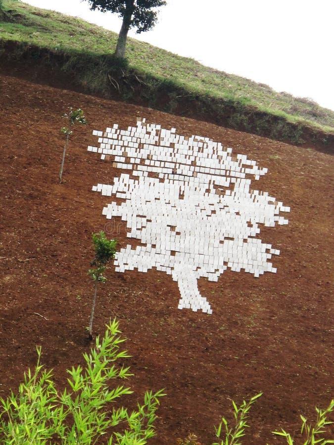 White silhouette a Land Art 1. Proccess of White silhouette a Land Art placed on the hill. Artist: Yudi Arif Budiman royalty free stock photos