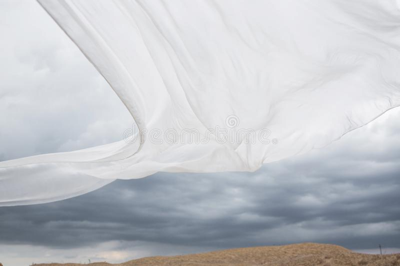 White silk blowing in the wind. Natural white silk fabric flying in the cloudy sky. Nobody. Picture. Abstract background royalty free stock images