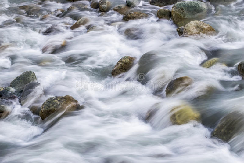 White silky water flowing downstream over the rocks and boulders royalty free stock photo