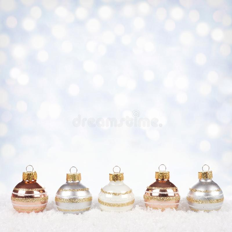 White, silver and gold Christmas ornaments in snow royalty free stock image