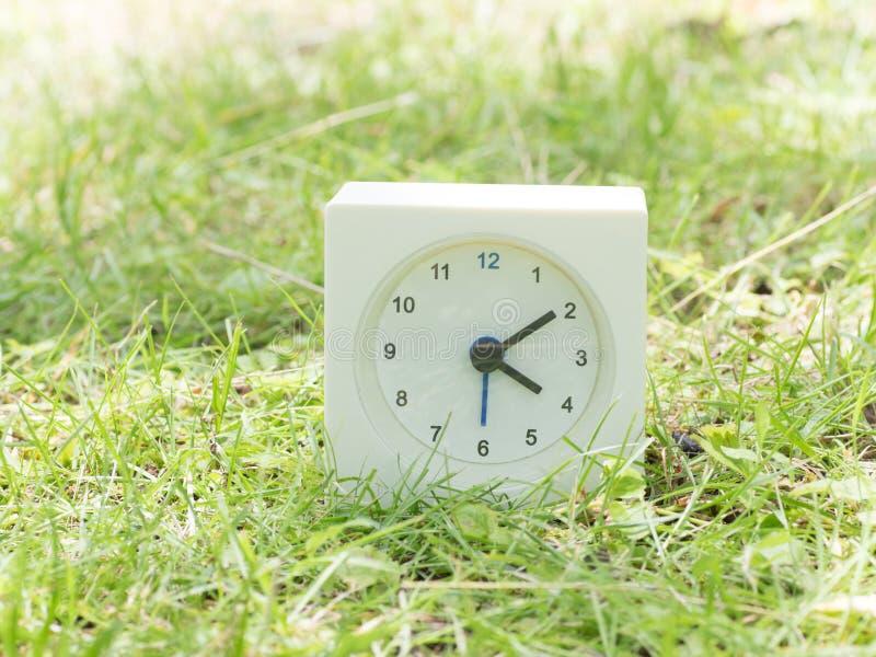 White simple clock on lawn yard, 4:10 four ten. White rectangle simple clock on lawn yard, 4:10 four ten stock image