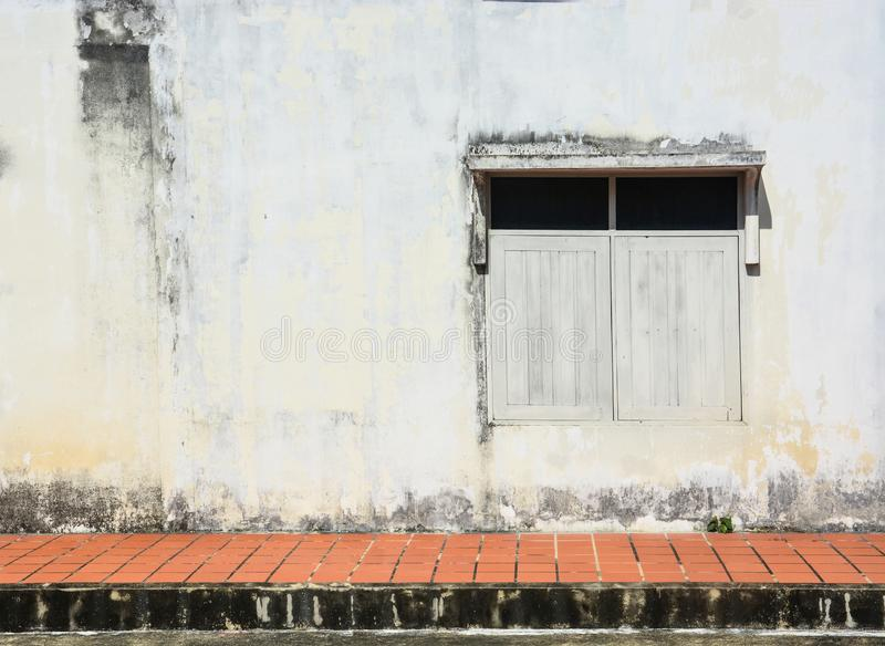 White simple vintage window with awning on grunge cement wall background and tiled pavement, copy space. White simple vintage window with awning on grunge cement royalty free stock photography