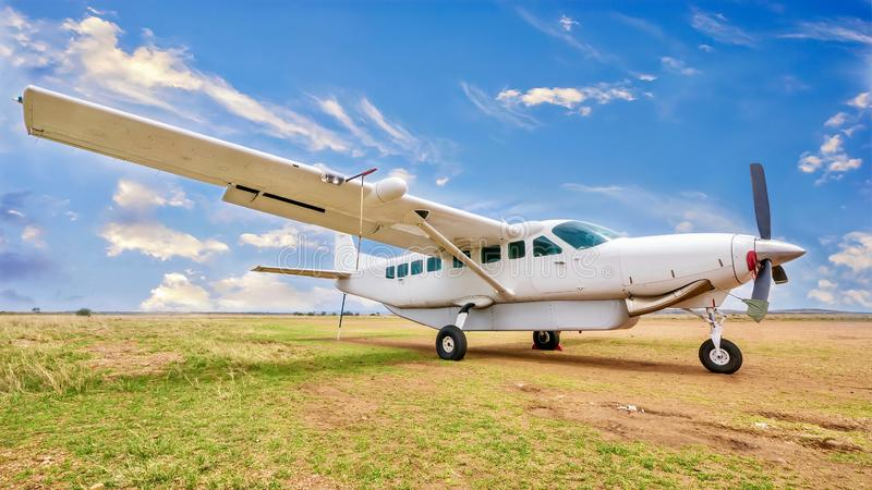 A small white private charter plane in an African landscape. A white, single engine charter plane sits on a grass and dirt landing strip in a beautiful and stock photo