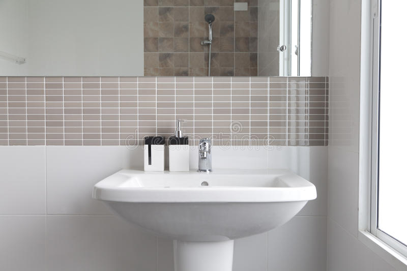 White sink in bathroom. White sink and dispenser in bathroom stock image