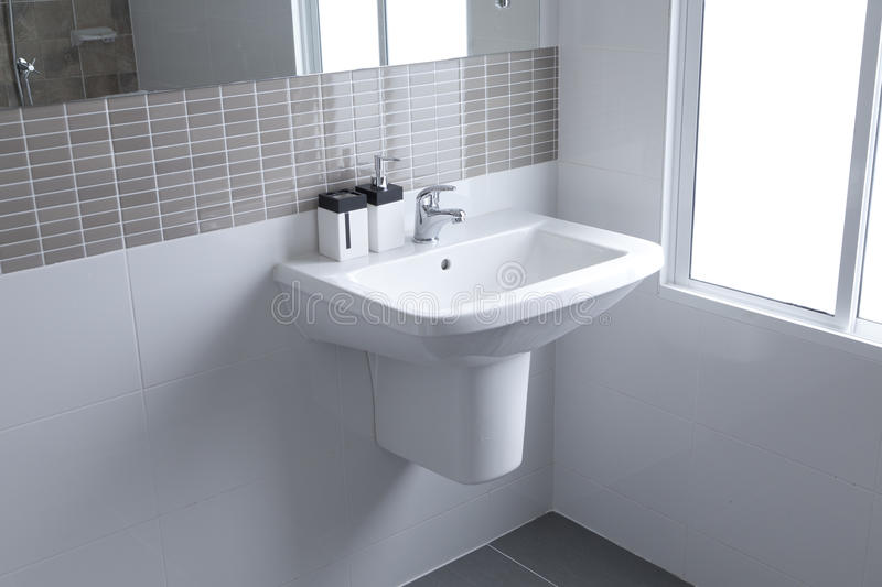 White sink in bathroom. White sink and dispenser in bathroom stock images