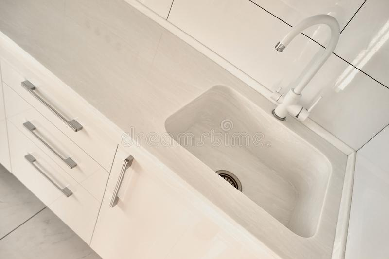 White sink in renovated kitchen close up. royalty free stock images