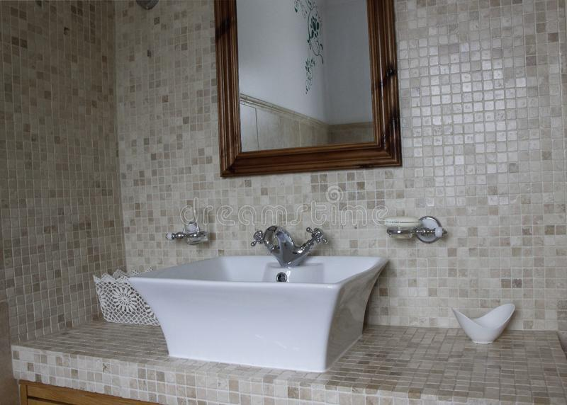 White sink with taps na tiled wall with a mirror stock images