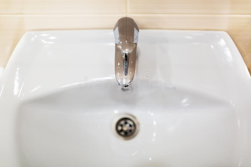 White sink or wash basin with shiny chromed faucet against the background of wall. Fragment of modern bathroom interio royalty free stock photos