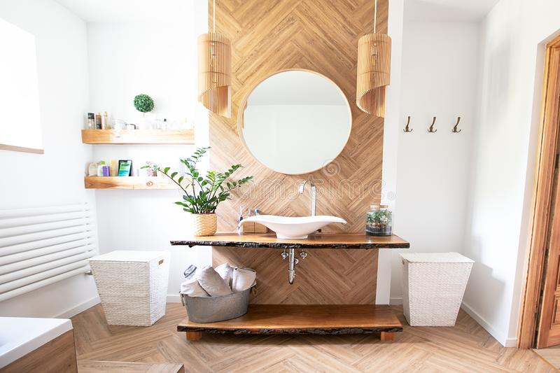 Boho style bathroom interior. White sink on wood counter with a round mirror hanging above it. Bathroom interior stock images