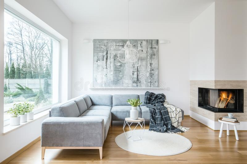 White sitting room interior with corner grey sofa, tulips in vase placed on end table, fireplace and modern art painting. White sitting room interior with grey royalty free stock images