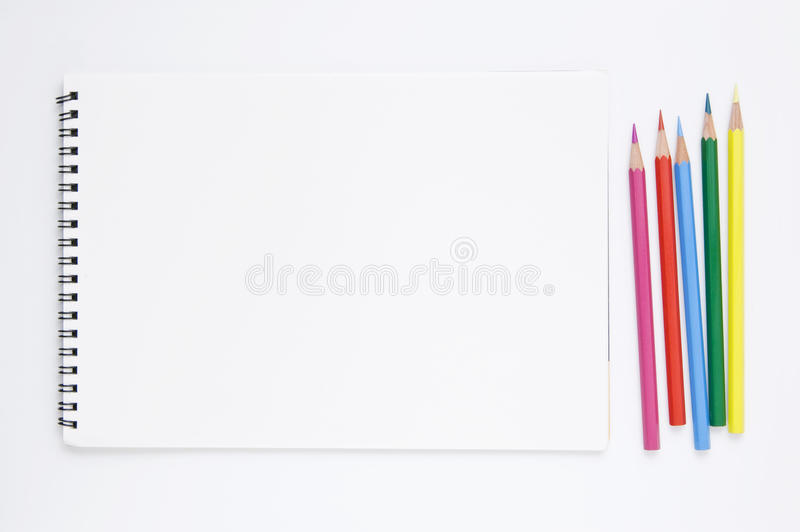 White sketchbook and color pencils stock images