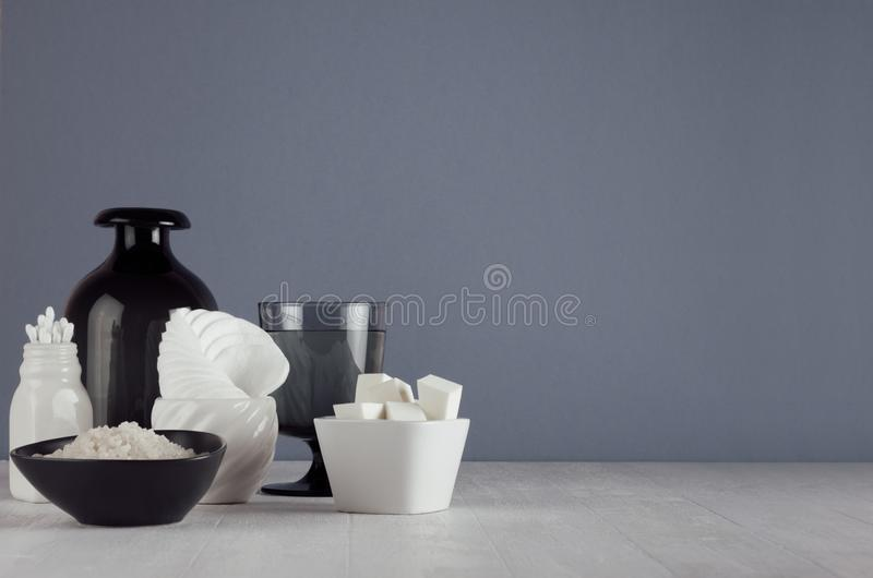 White skin care products and accessories on white wood shelf and dark grey wall, elegant bathroom decor. White skin care products and accessories on white wood stock photos