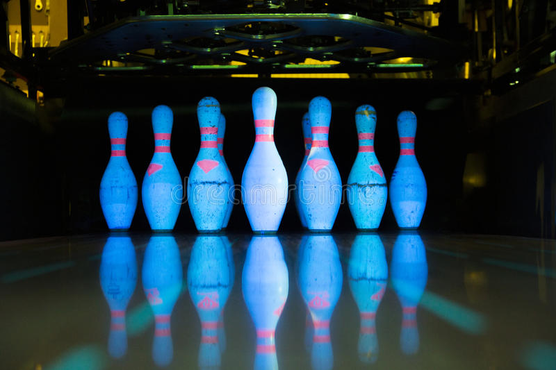 White skittles for bowling and their reflection. On the track royalty free stock image