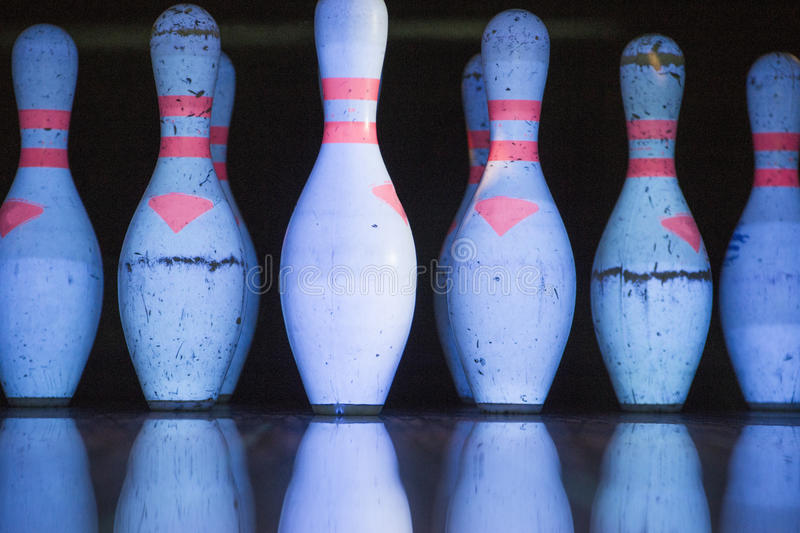 White skittles for bowling and their reflection. On the track stock images