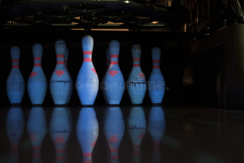 White skittles for bowling and their reflection. On the track royalty free stock photos