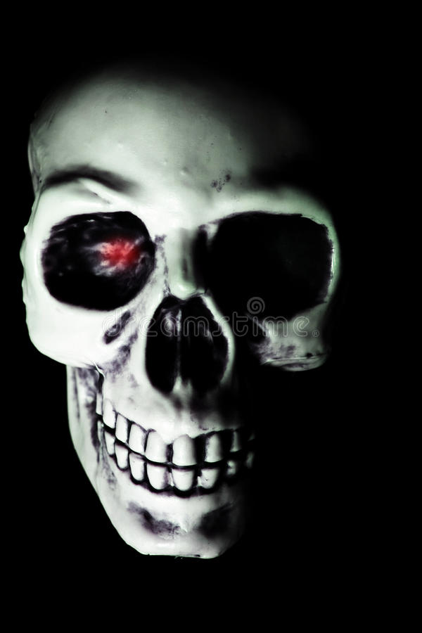 White Skull with Red Eyed Glow. A scary halloween skull staring with a red gleam in the eye royalty free stock images