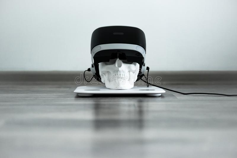 White skull on stand in VR helmet. Digital concept. stock images