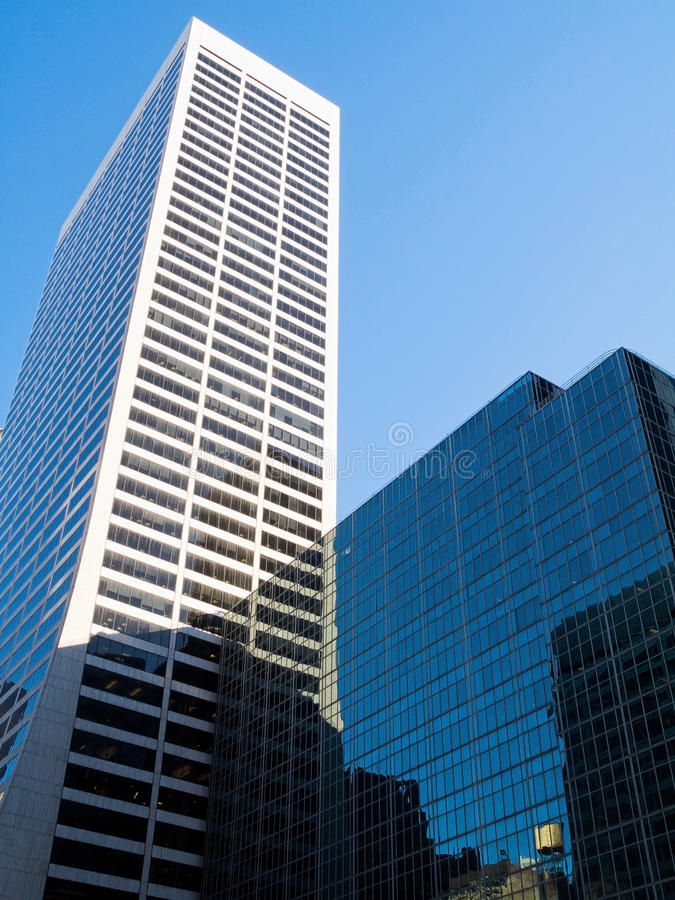 White Skyscraper. A tall white skyscraper and glass reflecting buikding in mid town Manhattan royalty free stock photo