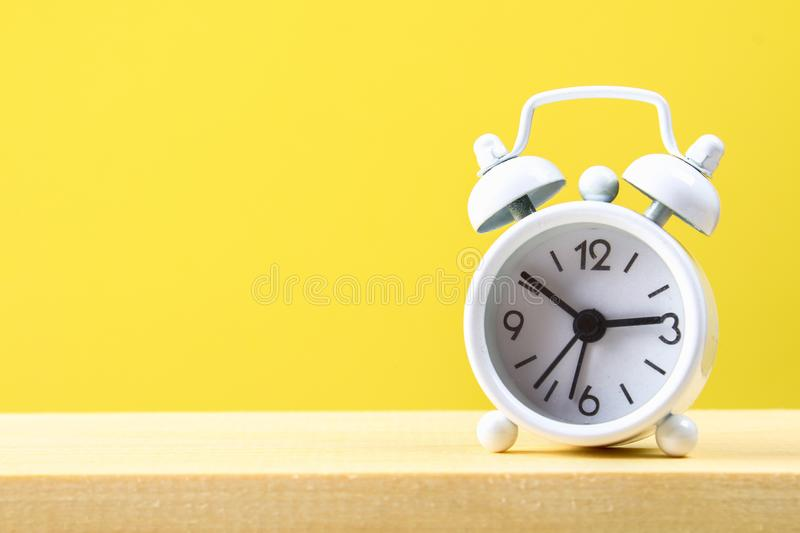White small alarm clock on a wooden shelf on a yellow pastel background. Minimalism. White small alarm clock on a wooden shelf on a yellow pastel background royalty free stock photography