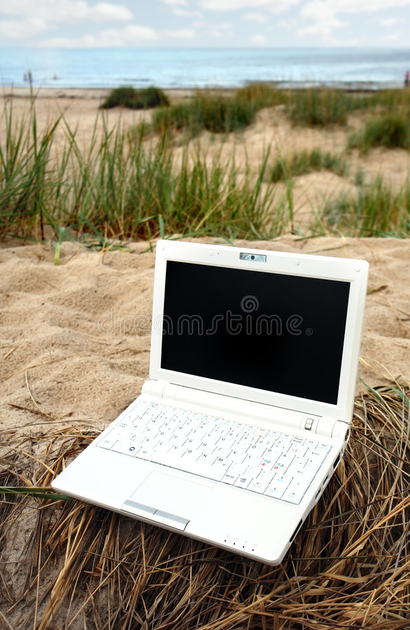 White small Laptop on the beach stock image