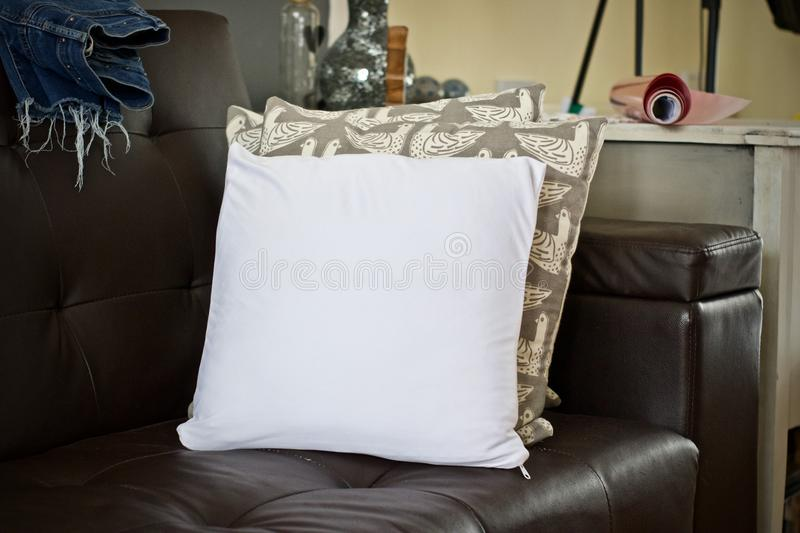 White small pillow mockup. White small pillow on the sofa. Living room mockup stock images