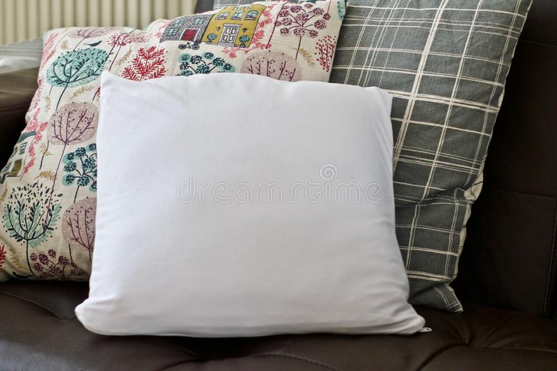 White small pillow mockup. White small pillow on the sofa. Living room mockup stock image