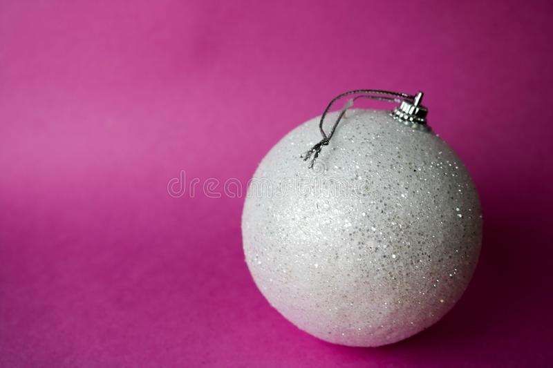 White small round glass plastic xmas festive Christmas ball, Christmas toy plastered over sparkles on a pink purple background. White small round glass plastic stock image