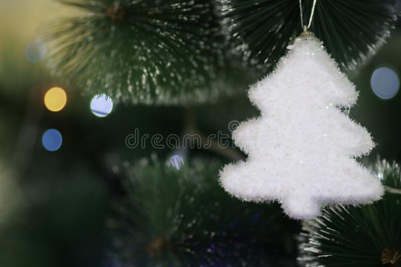 White small toy on a big Christmas Tree with a blurred lightning royalty free stock image