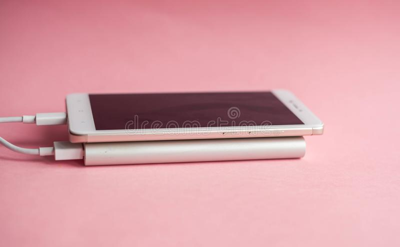 White smart phone charger with charger power bank on pink background royalty free stock image