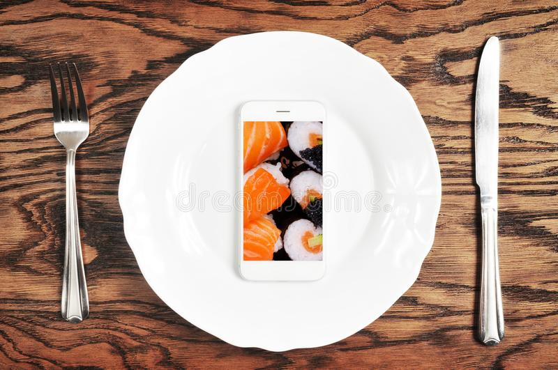 White smartphone with big screen on the plate with knife and for. White smartphone with big white screen on the plate with silver knife and fork on the dark royalty free stock photo