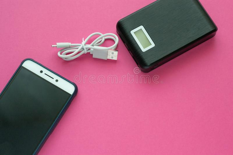 White smartphone in blue case in connection with black power bank on pink background. Travel technology concept royalty free stock photos