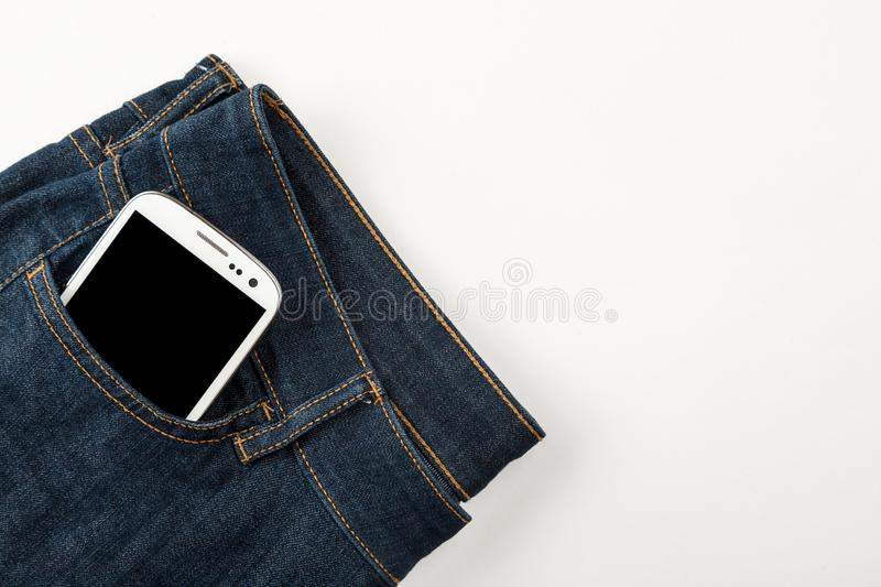 White smartphone in the blue jeans pocket closeup, top view stock photography