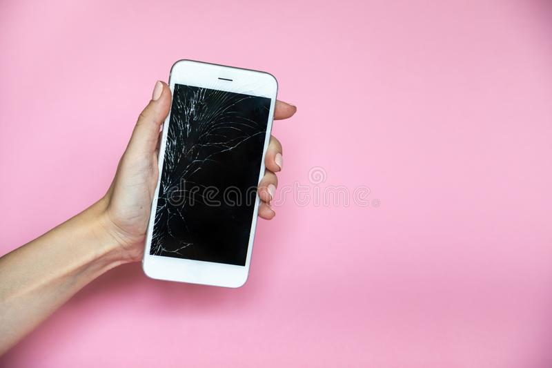 Smartphone with broken screen in hand on pink background stock photo