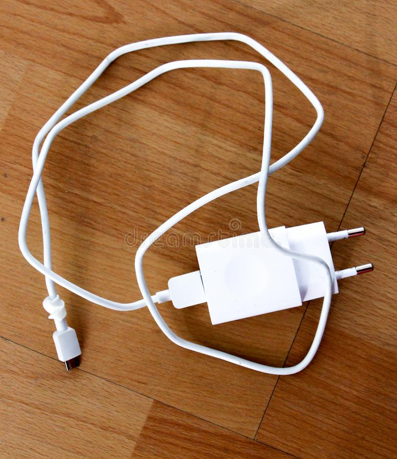 white smartphone charger on wood background royalty free stock photos