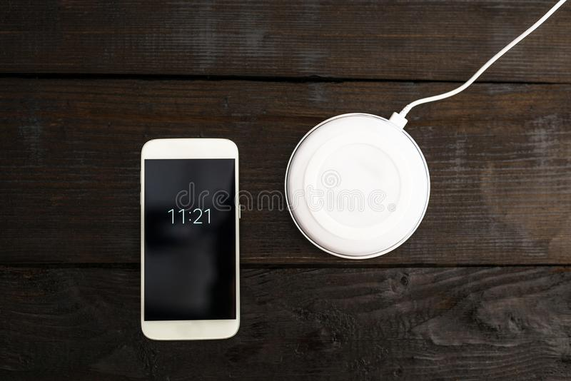White smartphone and charging pad. Wireless charging stock image