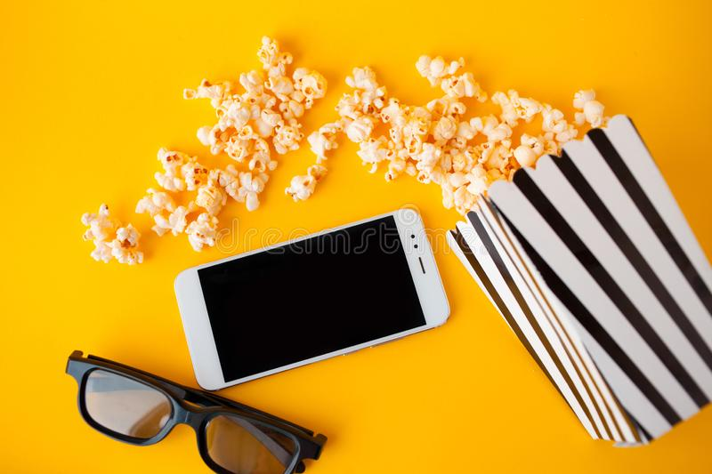 A white smartphone, 3d glasses, black and white striped paper box and scattered popcorn lie on a yellow background. stock photos