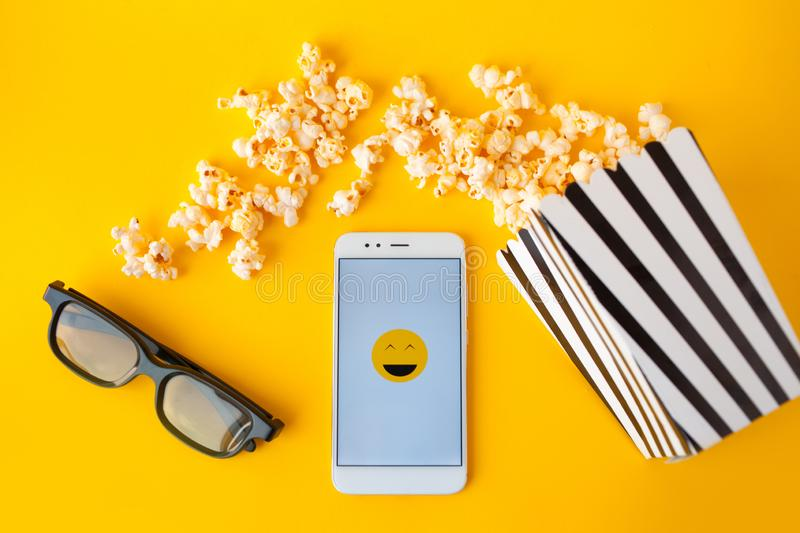 A white smartphone with smilies on the screen, 3d glasses, a black and white striped paper box and scattered popcorn stock photography