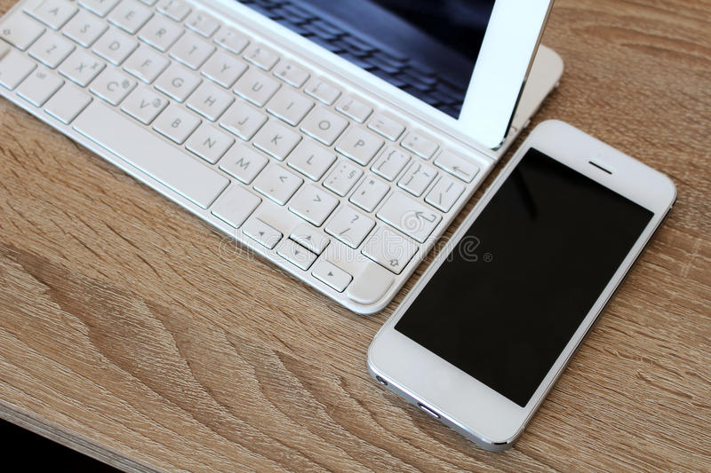 White smartphone and white tablet with keyboard stock photography