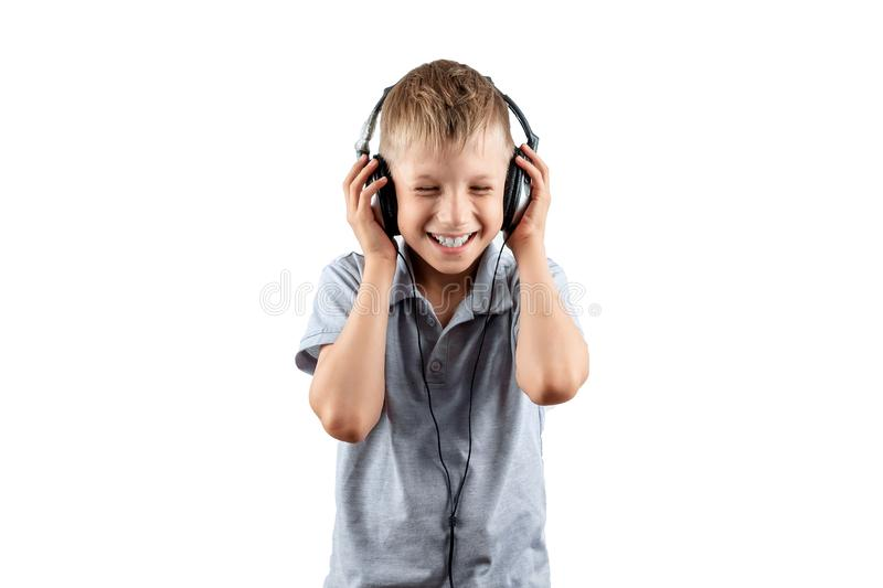 White smiling boy listens to music in big headphones Isolated on a white background. Musician, the future of the child, music. Lover royalty free stock photos
