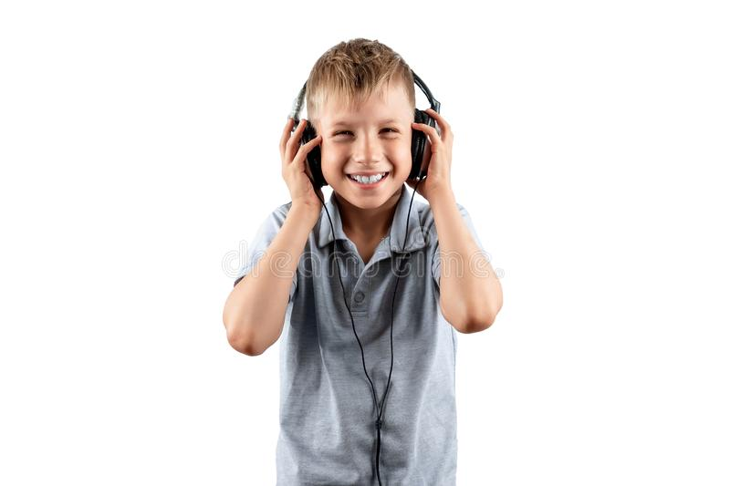White smiling boy listens to music in big headphones Isolated on a white background. Musician, the future of the child, music. Lover stock image