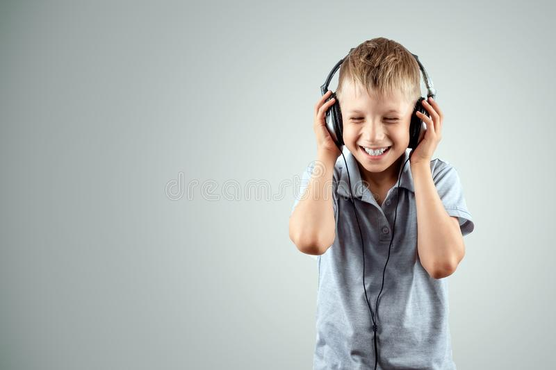 White smiling boy listens to music in large headphones on a light background. Musician, the future of the child, music lover.  royalty free stock photography