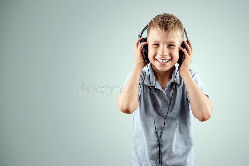 White smiling boy listens to music in large headphones on a light background. Musician, the future of the child, music lover stock images